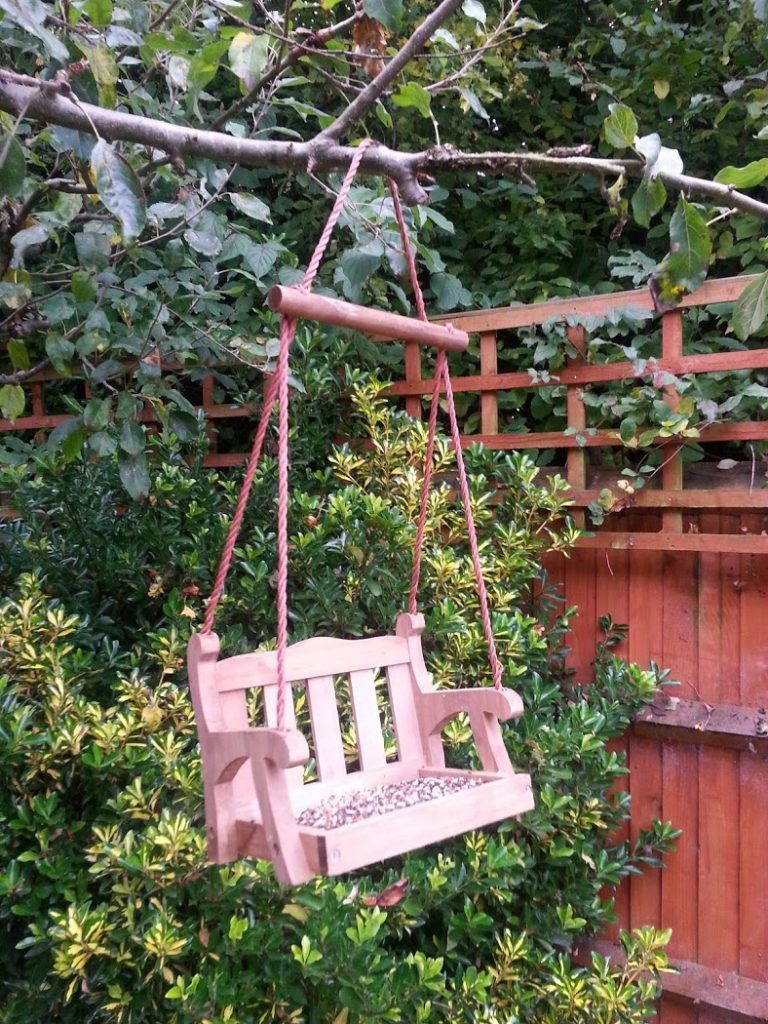 Feed the birds from a quirky wooden swing seat design bird feeder